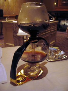 An all-glass coffee percolator.  The oil wick at the bottom is lit, which boils the water in the pot so that steam is driven up the center pipe and through the coffee grounds in the upper chamber.  When the heat is removed, the brewed coffee is sucked back down into the pot.
