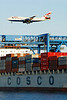 A British Airways 747 flys over the Container Ship COSCO Boston on approach to Logan Airport.