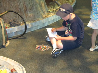 Doing the center's scavenger hunt. Writing down what he found out about the fire hose after he found it.