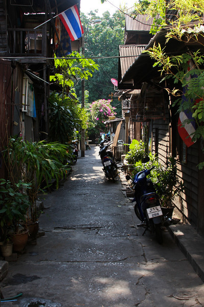 Motorcycles stand idle in a Bangkok alley.