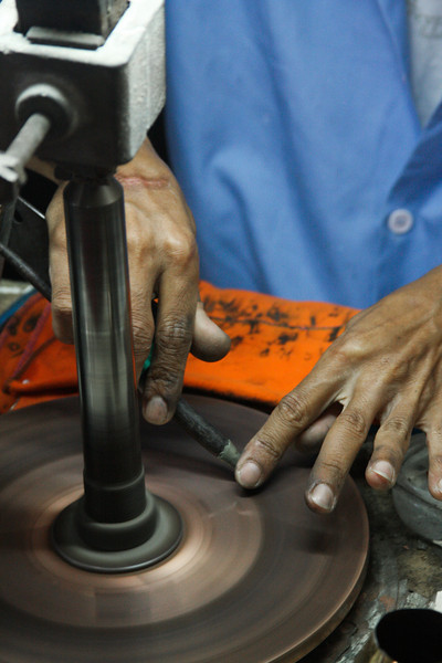 A Thai man works expertly grinding stones into fine jewelry at a local factory.