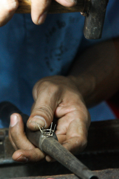 A hammer and a stick are the tools of the trade for a craftsman working on shaping the setting on a ring.