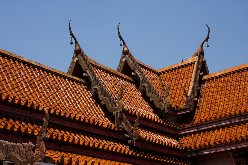 Glazed clay tiles shine under a midday sun from the roof of a Bangkok temple.