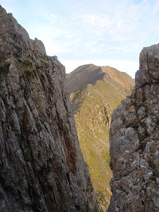 Crib Goch pinnacles. The path runs along the ledge at the top of the cliff to the left.