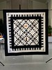 "Symphony is a black and white 70"" square  quilt made and quilted in 2009 by Gerry  McGuire.    Blocks have various musical  instruments with a piano key border.  This  quilt was inspired by the various instruments  played by her family including her 3 sons."