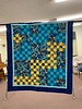 "Butterfly Buzz was made in 2009 by Helen  Gugeler.  This blue and yellow beauty was  machine pieced and hand quilted and  measures 44"" x 50""."