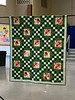 "This green with red rose center blocks is an  Irish Chain which Mary Throndson calls Irish  Rose.  It's 56"" x 65""and is machine quilted.   Mary bought the greens when traveling back  East and it fit right in with her wanting an  Irish Chain quilt."