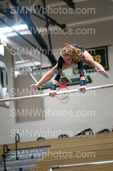 """Sophmore Amy Hein performs a straddle cast during the meet on Oct 8 at Lawrence Freestate.  Hein placed 3rd in uneven bars for JV competitors. """"Uneven bars is a physically demanding event.  It involves difficult positions and hard tension on your hands.  Advanced gymnasts wear grips to protect the hands,"""" Hein said."""