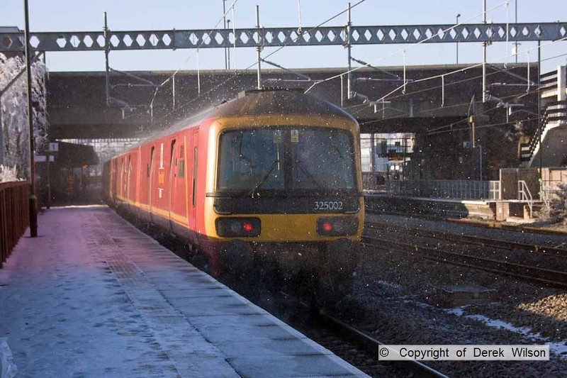 101207-022     Mail units, class 325 no's 325002 & 325015 speed through platform 1 at Tamworth, forming 1S07 Willesden-Shieldmuir. The speckles on the photo are caused by hoar frost being shook off the overhead wires.