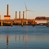 An inbound Eastern Route train and the New MWRA wind turbine on the Mystic RIver.