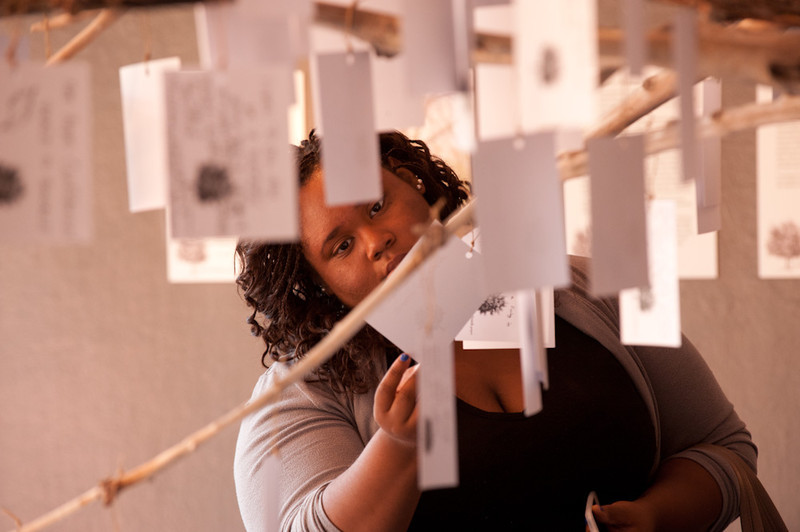 Student reads a hand-written message hanging from the Anne Frank Tree art installation during the 2011 Anne Frank Project at Buffalo State College.
