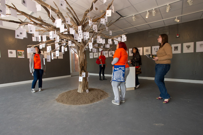 Students reading hand-written messages hanging from the Anne Frank Tree art installation during the 2011 Anne Frank Project at Buffalo State College.