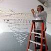 Artist Ben Perone adding origami birds to his art installation during the Anne Frank Project at Buffalo State.