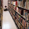 Student working in E.H. Butler Library Curriculum Materials stacks.