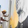 Buffalo State College alumni Edreys Wajed working on The Freedom Wall mural.