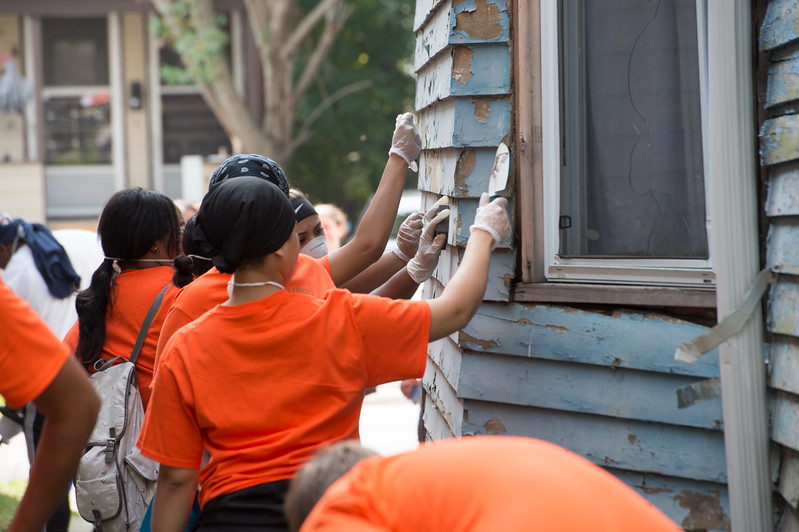 Students doing volunteer painting and clean up with It Takes a Village Action Organization during Bengal Dare to Care Day at Buffalo State College.