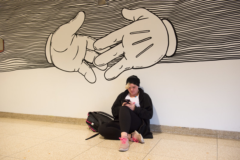 Student sitting under giant cartoon hands in the Upton Hall lobby at Buffalo State College.