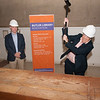 Provost Melanie Perreault and Library Director Charles Lyons take sledge hammers to the old circulation desk in the E.H. Butler Library at Buffalo State College.