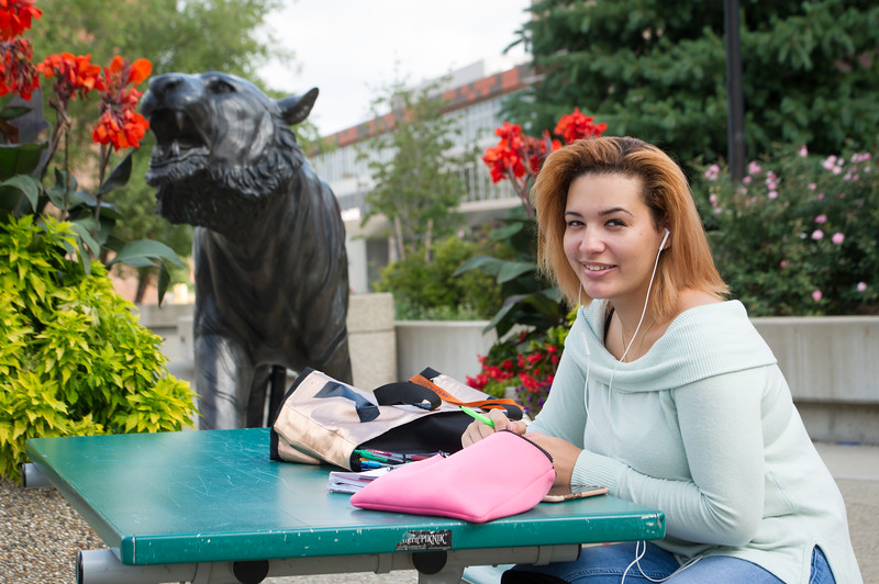 Student studying near bengal sculpture at Buffalo State College.