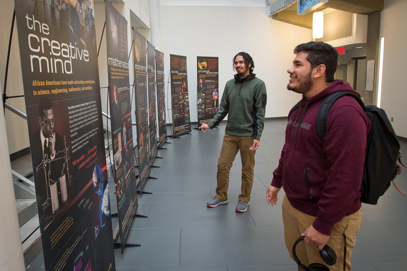 Students looking at African American Science History display in Science Building Atrium at Buffalo State College.