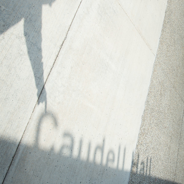 Shadow of Caudell Hall sign on sidewalk at Buffalo State College.