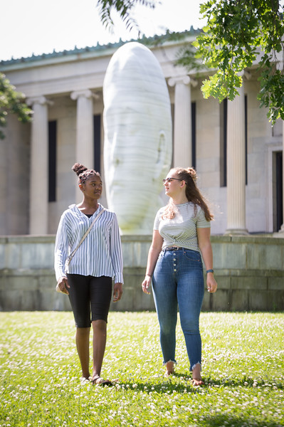Students talking in front of sculpture on the grounds of the Albright-Knox Art Gallery near Buffalo State College.