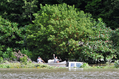 Some people exit their property by canoe as they paddle past a submerged full-size truck