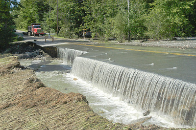 ERIC FRANCIS PHOTO A waterfall formed as a pair of culverts washed out and sent Whitman Brook over Quechee Main Street beside the golf course on Monday morning.