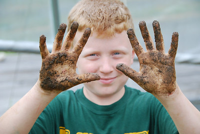 Boy with soil-covered hands