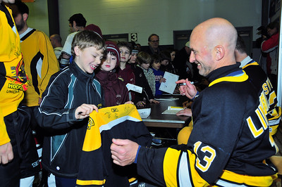 Boston Bruin Kenny Linesman signs a very happy fan's jersey.  Tim Gould photo.