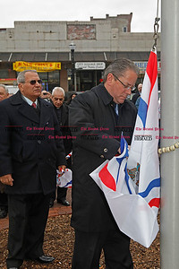 Chris Richie | Staff Mayor Timothy Stewart attaches the Assyrian flag next to Wilson Baba, board of advisor director, with AANF (Assyrian American National Federation) during the Assyrian flag raising ceremony celebrating the Assyrian new year 6761 in New Britain Central Park. (4/1/11)