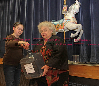 "Samantha Burr Ivy Drive School 5th grade student Kayla Savage donates coins for the fundrasier, ""Pennies for Ponies"", to bring a carousel to The New England Carousel Museum in Bristol.  Executive Director of the museum, Louise DeMars, collects the donations in the jar to start the fundraiser which will last until May 21. (4/1/11)"