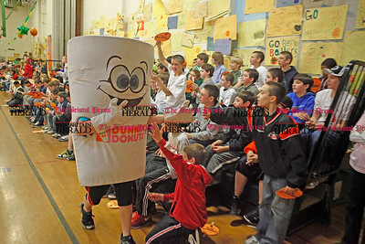 Chris Richie | Staff The Dunkin Donuts coffee mascot high-fives students during McGee Middle School's annual March Madness event, where funds raised by the students are given to charities and each grade plays a basketball game against the teachers. (4/1/11)