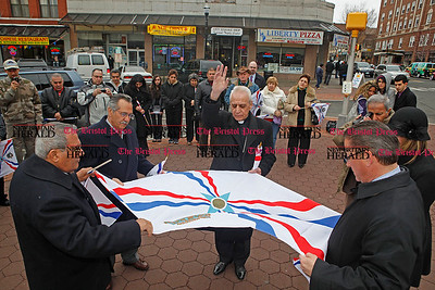 Chris Richie | Staff Core Bishop Aaron George blesses the flag during the Assyrian flag raising ceremony celebrating the Assyrian new year 6761 in New Britain's Central Park. (4/1/11)