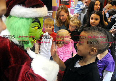 12/2/2011 Mike Orazzi | Staff Carmelo Thompson,4, greets the Grinch during a First Friday Family Festival- The Grinch event at the Imagine Nation Museum in Bristol on Friday evening.