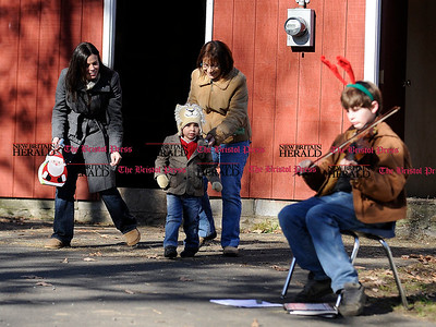 12/3/2011 Mike Orazzi | Staff Aaden Sehl,2, runs toward violin playing Tom Vaughn while walking with his mom Sandra Sehl and grandmother Kathie Felice at the Indian Rock Nature Center during Santa's petting farm on Saturday in Bristol. (names are CQ).