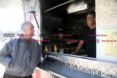 2/10/2011 Mike Orazzi | Staff Edward Wojnarski talks with street vendor Ken Meehan of Ken's Grille on North Main Street in Bristol on Thursday.