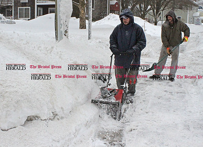 Samantha Burr Justin Root snowblows while coworker Adam Bellmar shovels for their company Collin's Total Home Care in Plainville. (2/1/11)