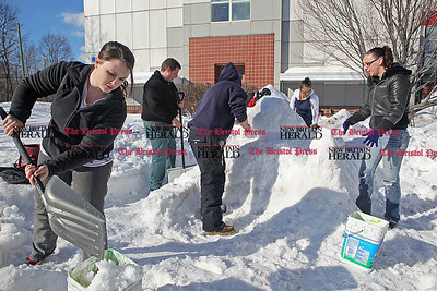 Chris Richie | Staff Kaitlyn McKnerey, left, and fellow art students create a sphinx and pyramids in the snow on the campus of CCSU in New Britain as a sign of solidarity to the uprising in Egypt. (2/10/11)