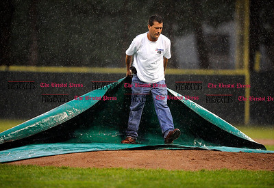 6/11/2011 Mike Orazzi | Staff A grounds keeper places the tarp on the pitcher's mound in the bottom of the 2nd during the Class LL Baseball Final at Muzzy Field in Bristol on Saturday night.