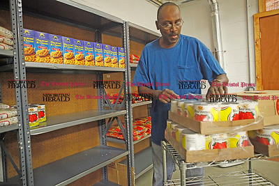 Chris Richie | Staff Volunteer Nate Brickhouse stocks shelves with non-perishable food items at the New Britain Food and Resource Center. (6/1/11)