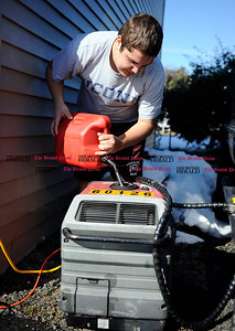 11/01/2011 Mike Orazzi | Staff Tom Simonin, 16, refills a generator at his parents home on Joseph Street in Bristol on Tuesday afternoon.