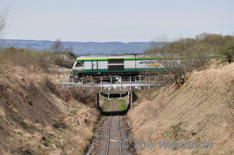 219 passes over the Bord na Mona Coolnamona railway to Clonkeen Bog to the south of Portlaoise. 219 was working the 1300 Heuston - Cork. Wed 06.04.11