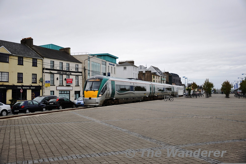 The Dublin to Rosslare Europort railway runs along Wexford Quay for half a mile south of the station at Wexford. This provides the unusual sight of a train running alongside the main street in the town. 22023 runs along the quay after departing Wexford Station with the 1025 Connolly - Rosslare Europort. Mon 25.04.11