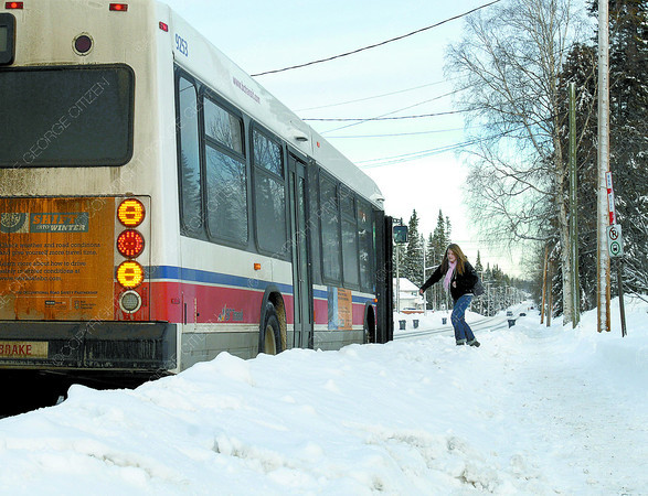 A passenger makes her way over the windrow to get into a transit bus at a stop on Highland Drive Thursday morning. Citizen photo by Brent Braaten