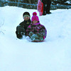 Citizen photo by Chuck Nisbett Aleksandra Babic, 4, and Landon Ingham, 8, have big smiles as they enjoy the latest snowfall at Carney Hill while Simo Babic surveys the hill Wednesday evening.