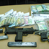 Citizen photo by Chuck Nisbett Over $40,000 in cash and weapons seized by PG RCMP Task Force members during a six month investigation into a high ranking member of the Game Tight Soldiers.