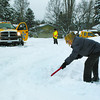 Citizen photo by Chuck Nisbett Shelley Ward digs out her driveway as two 5 Star tow trucks try to extricate themselves from the excesses of snow on Fairview Crescent Thursday morning.  One tow truck had been called out to assist a fairview resident to get free and with that accomplished he discovered that he was unable to get out.  The second truck arrived to assist the first and a complex game of you scratch my back and I'll scratch yours took place to get both vehicles back out to assist waiting customers.