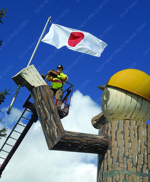 Aaron Bryant with Hazelwood Signs changes the flag on Mr. PG Wednesday afternoon to the Japanese flag. The change, in support of the Japan earthquake victims, was organized by Akira Goto from Sushi Factory Sendo. Hazzelwood signs donate there time and use of equipment needed to change  the flag. They are accepting donations at Sushi Factory Sendo in College Heirghts. Citizen photo by Brent Braaten