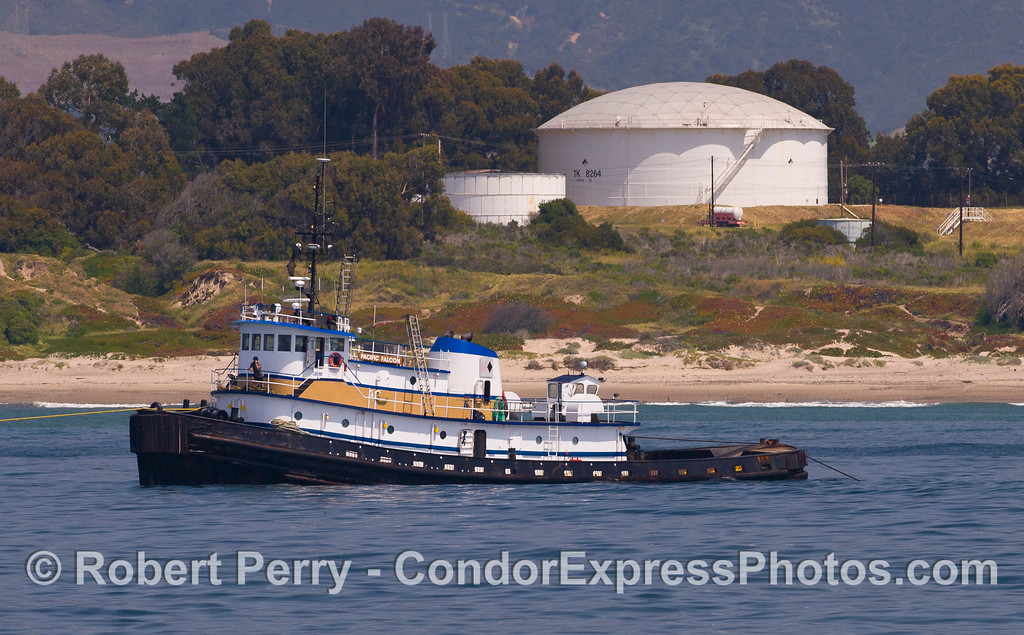 "The towboat ""Pacific Falcon"" is seen moored near the Elwood Oil storage tanks.  The Pacific Falcon takes a barge full of oil from platform Holly to LA Harbor (and more infrequently, to San Francisco)"